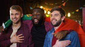 Amigos multiétnicos que apoyan el equipo portugués, el himno del canto y agitando la bandera metrajes