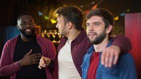 Amigos multiétnicos que escuchan el himno antes del partido de fútbol, tiempo de los resultados en pub almacen de metraje de vídeo
