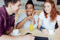 Amigos multiétnicos que hablan en café Fotos de archivo