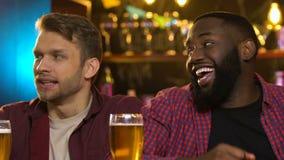 Amigos multiétnicos que miran el juego del deporte en el pub, animando para diversos equipos almacen de metraje de vídeo