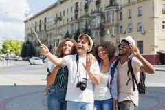 Amigos multiétnicos que registran el vídeo con el monopod al aire libre imagen de archivo libre de regalías