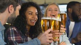Amigos multiétnicos que tintinean la cerveza, celebrando meta preferida del equipo de deportes, liga metrajes