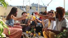 Amigos multi-étnicos alegres que riem e que brindam com os cocktail no telhado video estoque