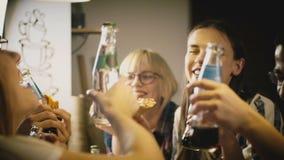 Amigos multi-étnicos felizes que fazem um brinde ao comer a pizza na festa em casa ocasional Os jovens passam o tempo do divertim vídeos de arquivo