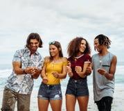 amigos Multi-étnicos que gozan en la playa con las bengalas imágenes de archivo libres de regalías