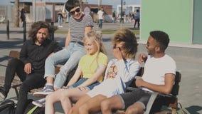 Amigos multi-étnicos satisfeitos no banco da rua filme