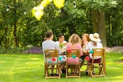 Amigos multiculturais que sentam-se na tabela e que falam em GA imagem de stock royalty free