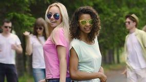 Amigos multiculturales hermosos que bailan y que se ríen del disco en el parque, verano metrajes