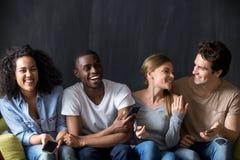 Amigos multirraciais de riso que têm o divertimento junto, guardando telefones foto de stock
