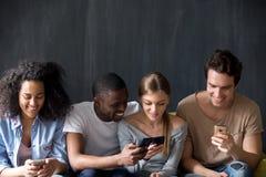 Amigos multirraciais de sorriso que usam telefones junto, compartilhando da notícia fotografia de stock royalty free