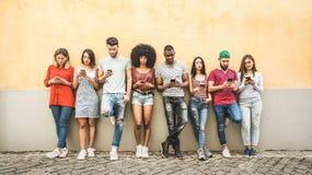 Amigos multirraciais que usam o smartphone contra a parede na universidade foto de stock