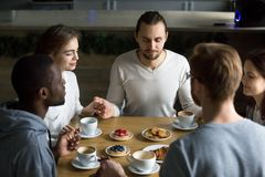 Amigos multirraciales agradecidos que se sientan junto en el sayi de la tabla del café imagen de archivo
