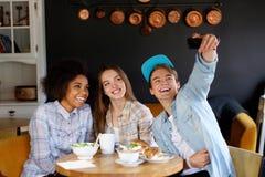Amigos multirraciales alegres que toman el selfie en un café Fotografía de archivo libre de regalías