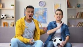 Amigos multirraciales ansiosos infelices con el equipo de fútbol nacional que pierde, ocio almacen de metraje de vídeo