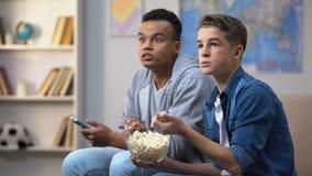 Amigos multirraciales ansiosos que comen las palomitas y que miran al programa de televisión, tiempo libre almacen de metraje de vídeo