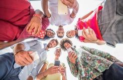 Amigos multirraciales con los teléfonos elegantes Fotografía de archivo