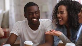 Amigos multirraciales felices de la gente joven que hablan riéndose de la reunión de grupo almacen de video