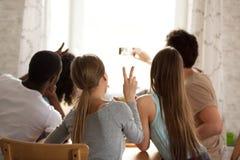 Amigos multirraciales felices de la vista posterior que hacen el selfie, vídeo de registración foto de archivo libre de regalías