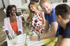 Amigos multirraciales jovenes en el café Foto de archivo