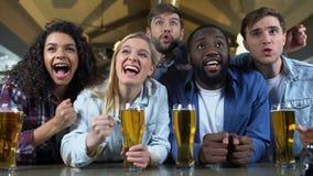 Amigos multirraciales jovenes que arraigan para el equipo preferido, pub de observación del campeonato almacen de metraje de vídeo
