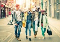 Amigos multirraciales que caminan en carril del ladrillo en Londres Shoreditch foto de archivo