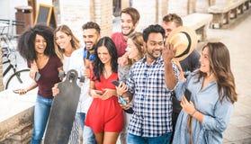 Amigos multirraciales que caminan y que hablan en el centro de ciudad - g feliz Imagenes de archivo