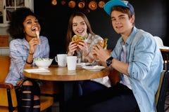 Amigos multirraciales que comen en un café Fotografía de archivo