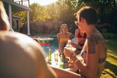 Amigos multirraciales que gozan en el partido del poolside fotografía de archivo libre de regalías