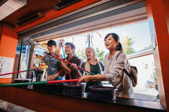 Amigos multirraciales que juegan al juego de arcada en el parque de atracciones imagen de archivo libre de regalías