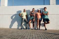 Amigos multirraciales que presentan al aire libre por una pared imagen de archivo
