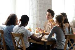Amigos multirraciales que tienen conversación y que comen la pizza en café imágenes de archivo libres de regalías