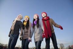 Amigos na pista de gelo, guardando as mãos e o sorriso Imagem de Stock
