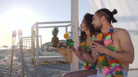 Amigos na praia, em grinaldas coloridas no amor do pescoço assentado no mar da costa, em homem e em amiga no luminoso de raios do vídeos de arquivo
