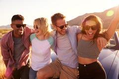Amigos na viagem por estrada que senta-se em Hood Of Convertible Car imagem de stock royalty free