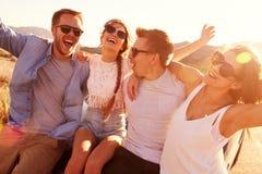 Amigos na viagem por estrada que senta-se em Hood Of Convertible Car imagens de stock royalty free