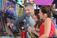 Amigos no casino na máquina de entalhe Fotografia de Stock Royalty Free