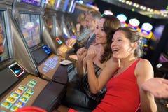 Amigos no casino na máquina de entalhe foto de stock royalty free