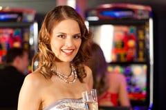 Amigos no casino na máquina de entalhe Imagens de Stock