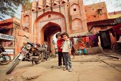 Amigos no identificados de los niños que se divierten en área pobre de la gente con las calles apretadas Imagen de archivo