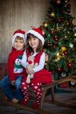 Amigos no Natal - dois caçoam, sentando-se em um pequeno trenó interno, sorrindo Imagens de Stock Royalty Free