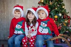 Amigos no Natal - três caçoam, sentando-se em um pequeno trenó interno, sorrindo Foto de Stock Royalty Free