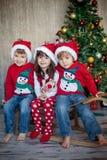 Amigos no Natal - três caçoam, sentando-se em um pequeno trenó interno, sorrindo Fotografia de Stock
