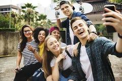 Amigos no parque que toma um selfie do grupo milenar e a juventude c foto de stock