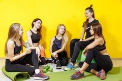 Amigos no sportswear que falam e que riem junto ao sentar-se no assoalho de um gym após um exercício fotos de stock