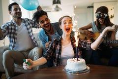 Amigos novos alegres que têm o divertimento no partido Fotografia de Stock Royalty Free