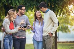 Amigos novos de sorriso felizes que andam fora no parque que guarda a tabuleta digital imagem de stock