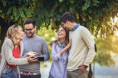 Amigos novos de sorriso felizes que andam fora no parque que guarda a tabuleta digital fotos de stock