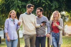 Amigos novos de sorriso felizes que andam fora no parque que guarda a tabuleta digital imagem de stock royalty free