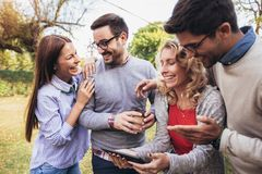 Amigos novos de sorriso felizes que andam fora no parque que guarda a tabuleta digital foto de stock