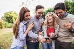 Amigos novos de sorriso felizes que andam fora no parque que guarda a tabuleta digital imagens de stock